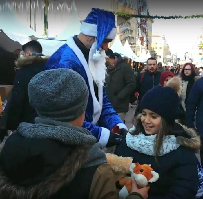 Die Kinder freuen sich über die Geschenke vom blauen Weihnachtsmann